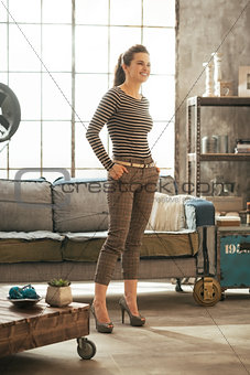 Full length portrait of happy young woman standing in loft apart