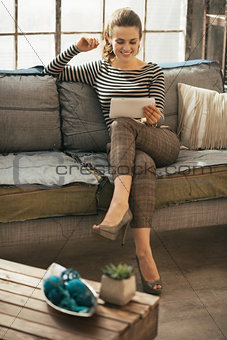 Happy young woman using tablet pc in loft apartment
