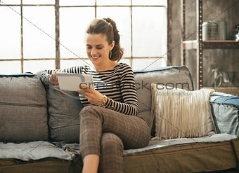 Smiling young woman using tablet pc in loft apartment
