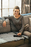 Happy young woman sitting on sofa and using tablet pc in loft ap