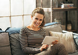 Smiling young woman sitting on sofa and using tablet pc in loft