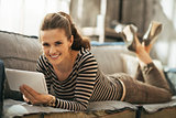Smiling young woman laying on couch and using tablet pc in loft