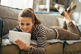 Happy young woman laying on couch and using tablet pc in loft ap