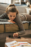 Young woman laying on couch and using tablet pc in loft apartmen