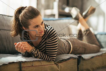 Young woman laying on divan in loft apartment