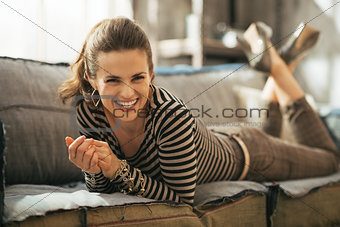Portrait of smiling young woman laying on divan in loft apartmen