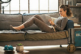 Happy young woman laying on divan and using tablet pc in loft ap