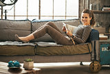 Smiling young woman laying on divan and using tablet pc in loft