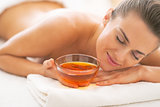 Relaxed young woman laying on massage table with honey plate