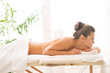 Relaxed young woman laying on massage table