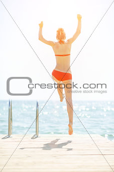 Young woman jumping from bridge into sea. rear view