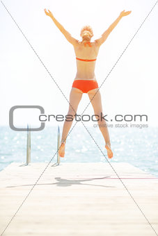 Young woman jumping on bridge. rear view