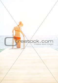 Young woman going down into sea from bridge. rear view