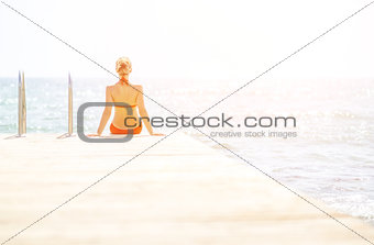 Young woman sitting on bridge. rear view