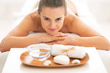 Young woman laying on massage table near spa therapy ingredients