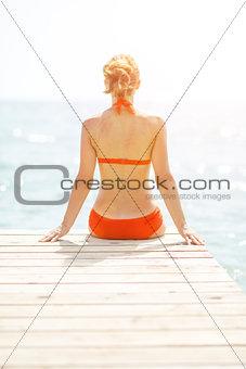 Young woman sitting on bridge. rear view