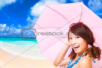 beauty woman holding a umbrella with beach background