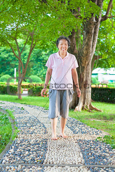 asian older woman walking on the stone walkway