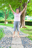 happy grandmother standing on stone walkway and raise hands