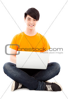 happy young student sitting on floor and  using laptop