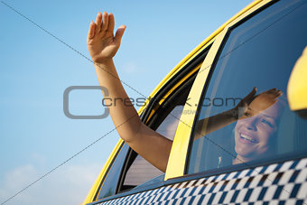woman in taxi waving hand out of car window