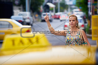 people travelling-business woman stopping yellow taxi
