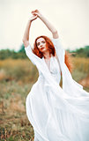 Beautiful redhead woman wearing white dress in a field