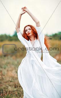Beautiful redhead woman wearing white dress in a field