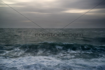 Moody seascape of waves breaking UNDER STORMY wINTER SKY