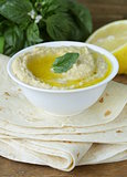 traditional hummus dip of chickpea with pita bread on a wooden table