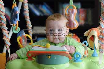 Cute young baby surrounded by toys