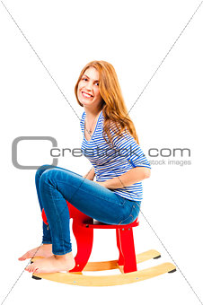 cheerful girl in a baby rocking chair in the studio