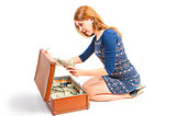 Surprised girl found in a suitcase of money