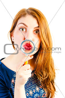 cheerful girl fooling around with a magnifying loupe