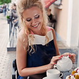 a beautiful young blond girl in summer dress at the table