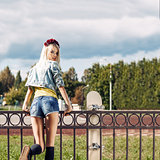 Blonde girl in short denim shorts with roses wreath on head