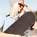 Beautiful blonde girl in beanie hat and leopard sunglasses with
