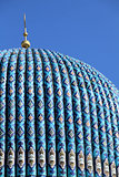 Tiled dome of a mosque with a golden crescent