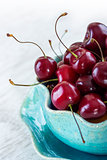 fresh red cherries on a blue plate