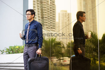 Portrait of chinese office worker with coffee cup