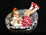 little girl with a soft toy on chair