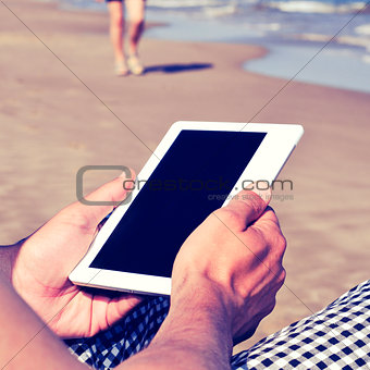 man using a tablet or an e-book on the beach