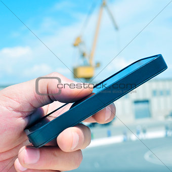 man using a smartphone in an industrial park