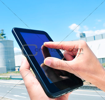 man using a tablet in an industrial park