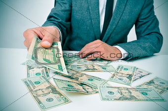 man in suit giving dollar bills