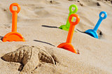 starfish sand and toy shovels of different colors on the sand