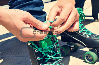 young man tying his roller skates