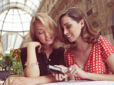 women look at message on mobile phone