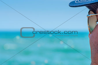 Unshaven man in sunglasses looking at sea