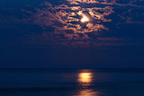 Full moon in night sky over moonlit water